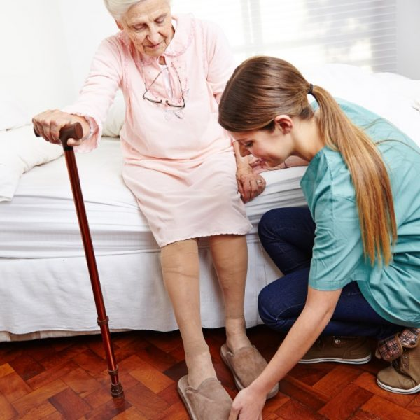 Nurse helping older woman put on shoes (Medium) - Aged Care & NDIS Newcastle - Extracare Home Services